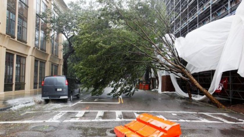 A van squeezes past a partially fallen tree on Meeting Street as Hurricane Matthew hits Charleston, South Carolina