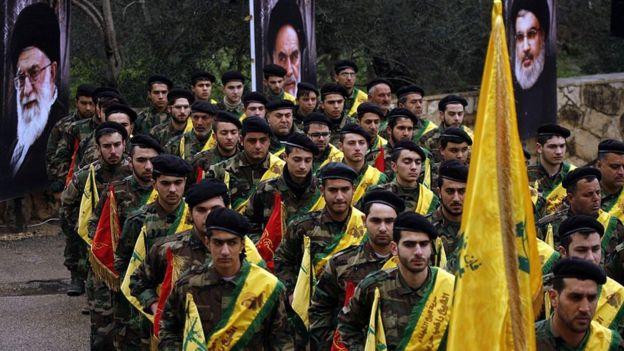 Combatientes de Hezbollah marchan frente a las imágenes de líderes de Irán y Hezbollah