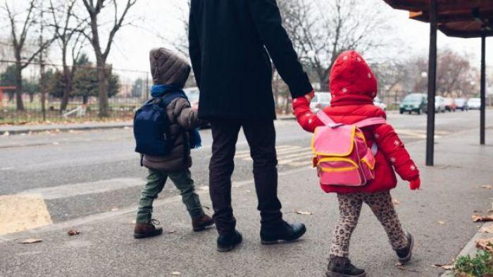 Man walking children to school