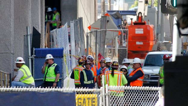 Construction workers gather at the base of the Wilshire Grand Tower on South Figueroa Street where a worker fell to his death