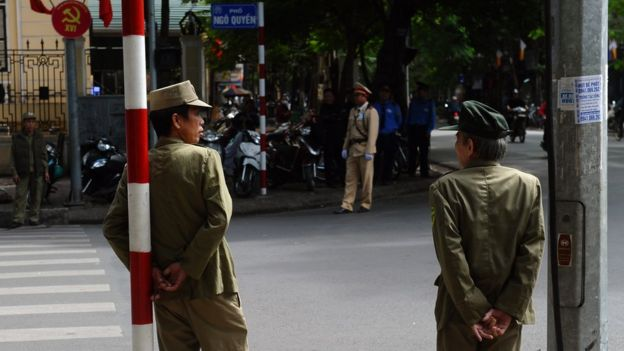 Police and militiamen stand guard at an intersection where buses transporting delegates attending a local communist party congress are expected to ride past in downtown Hanoi on November 2, 2015.