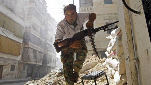 Un combatiente rebelde se cubre durante enfrentamientos con el ejército sirio en el distrito de Salahuddin de Alepo (7 de agosto de 2012)