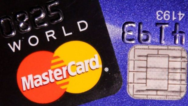 A MasterCard credit card is pictured next to a computer chip on a bank card