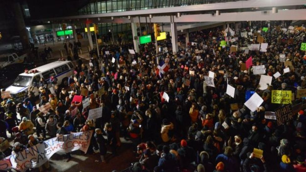 Protestors rally during a demonstration against the new immigration ban issued by President Donald Trump at John F. Kennedy International Airport on January 28, 2017 in New York City.