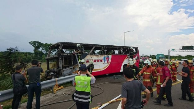 A handout photo released by the Taoyuan City Fire Department show police and firemen inspect the scene of a tourist coach fire near the Taoyuan Internatinal Airport in Taoyuan County outside Taipei, Taiwan, 19 July 2016.