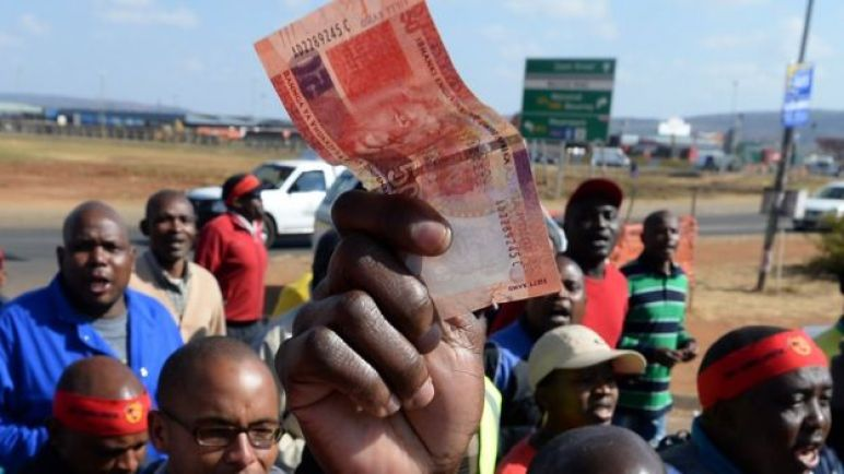 Someone holding a rand note.