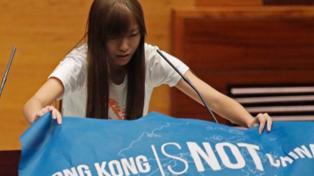 A newly elected lawmaker, Youngspiration's Yau Wai-ching, displays a banner with words reading