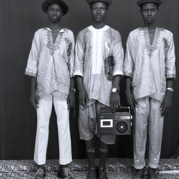 Three Malian men stand holding a boombox looking very serious