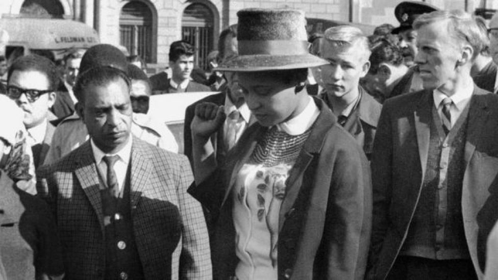 Winnie Mandela leaves the Palace of Justice in Pretoria with her fist clenched, after the verdict of the Rivonia Trial was given