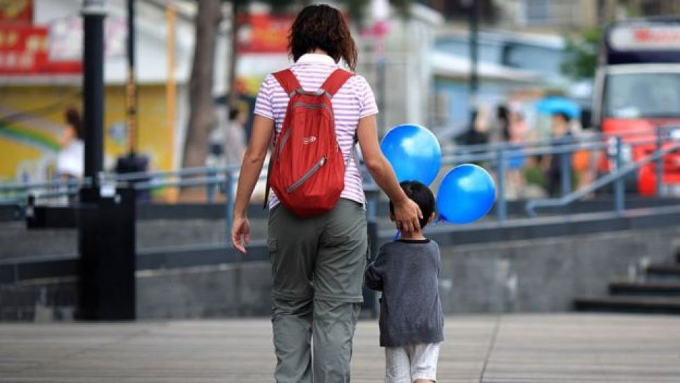 A woman walks with a child holding balloons in Hong Kong