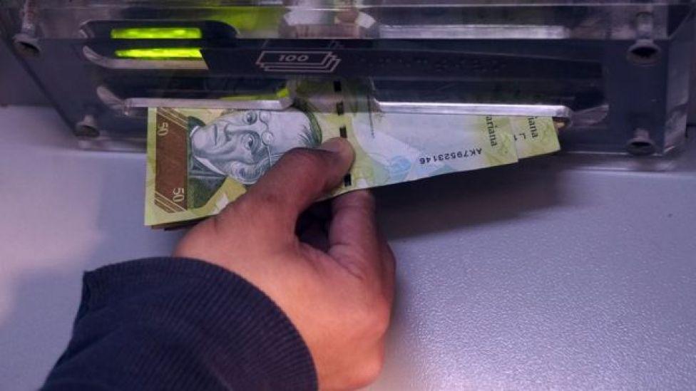 Una mano agarra los billetes del cajero automático