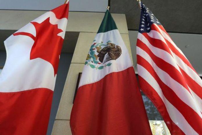 Banderas de Canadá, México y Estados Unidos.