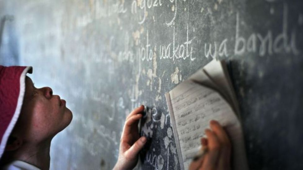 Because of their low vision, children with albinism struggle to read the blackboard in class
