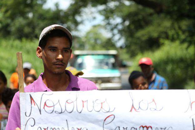 Junger Mann am von Menschen errichteten Straßensperre, die allein auf Mangos überlebenden wurden