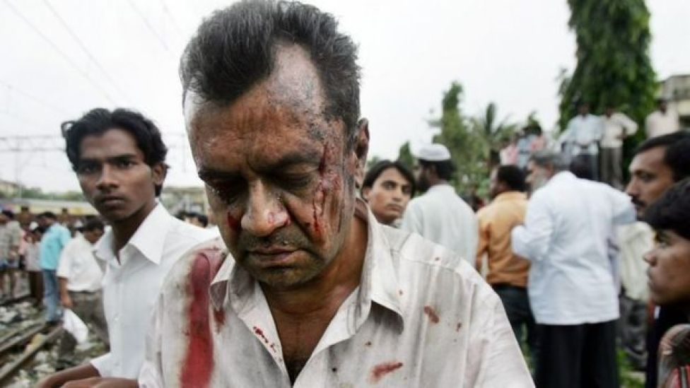 An unidentified person who was injured in a bomb blast at the Mahim railway station walks away from the site, in Bombay, India, Tuesday, July 11, 2006.