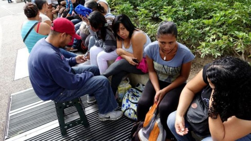 people queue to try to buy groceries and goods outside a supermarket in Caracas on 11 November