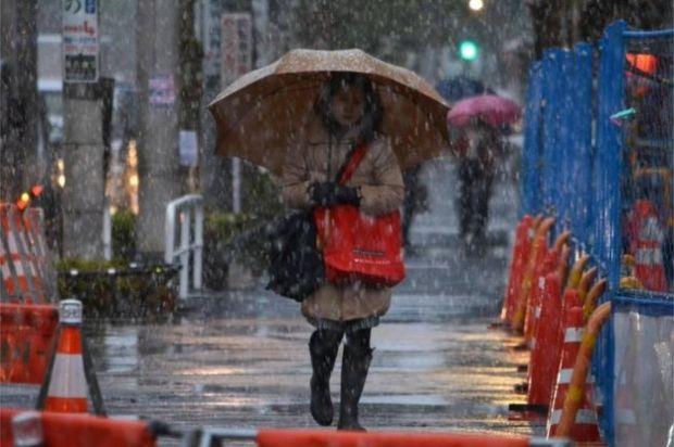 A woman walks through snow in Tokyo