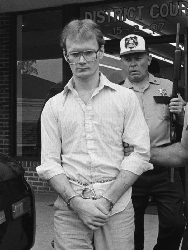 Nick Yarris esposado junto a un oficial de policía armado.