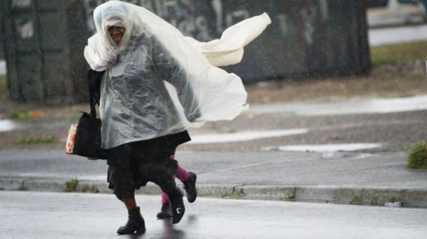 A woman and a child run across the road, in makeshift raincoats in an informal settlement, in Langa, during one of the most intense storms that has hit the Western Cape Province in more than a decade, on June 07, 2016, in Cape Town