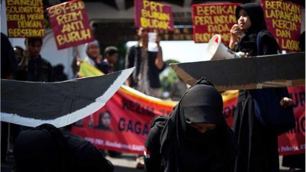 Protesta en la que se ve a dos mujeres vestidas con una burka y sobre ellas penden dos espadas hechas de cartón.