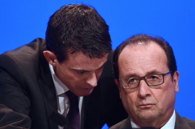 French Prime Minister Manuel Valls (L) speaking to French President Francois Hollande before he delivers a speech during a meeting of French mayors in Paris, 18 November