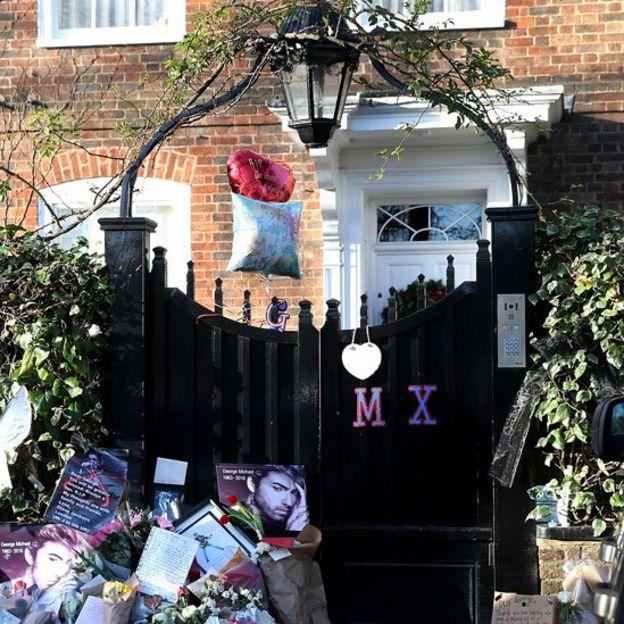 Flores y otros tributos a la puerta de la casa de George Michael en Londres