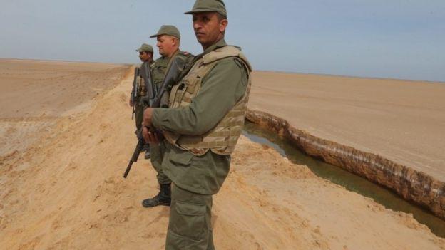 Tunisian soldiers stand on a sandbank during a presentation of the anti-jihadi fence, near Ben Guerdane, eastern Tunisia