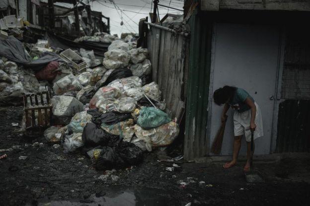 Una mujer barre la calle frente a su casa en Happyland, junto a un vertedero de basura en Tondo, Manila.