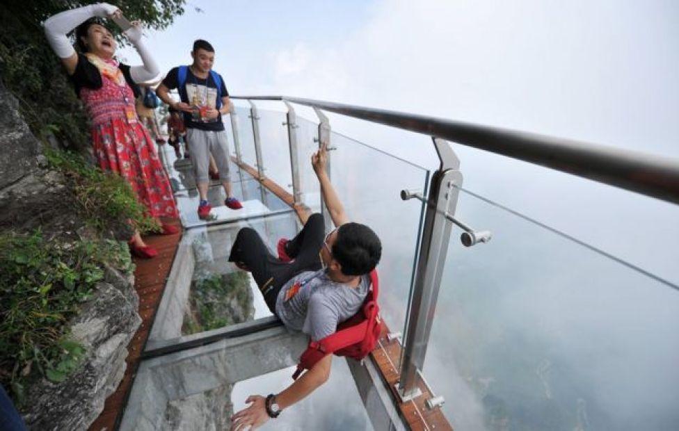 Gente tomándose fotos en el puente de cristal.