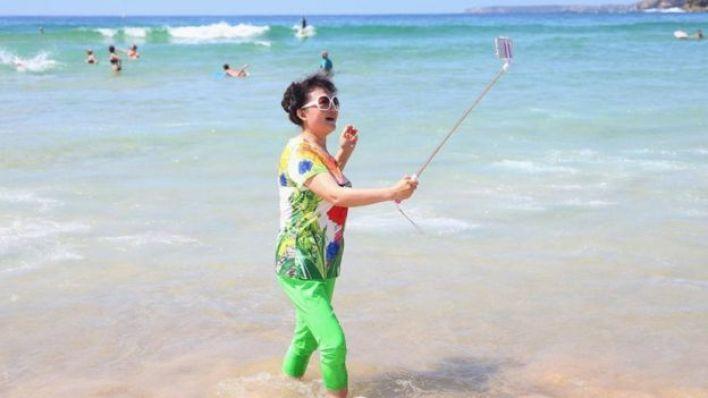 فتاة تلتقط صورة سيلفي على شاطئ البحر