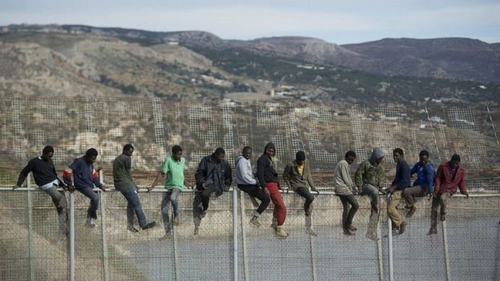 African migrants attempt to scale the fence at the border between Morocco and the North African Spanish enclave of Melilla