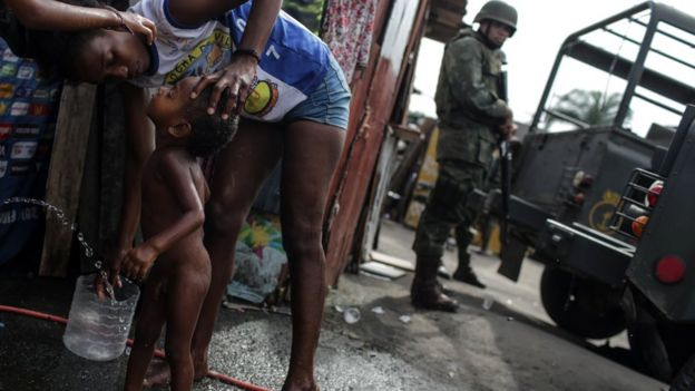 Mãe dá banho no filho na rua, perto de um militar armado