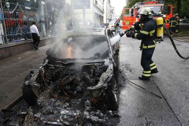 A firefighter works at the scene where a number of cars burnt down during the G20 summit in Hamburg, Germany, 7 July