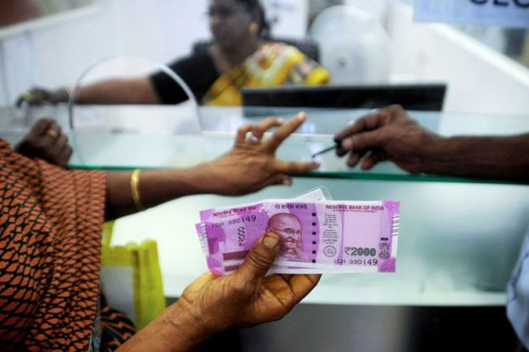 In this photograph taken on November 17, 2016, an Indian woman holds 2000 INR notes as she has her finger marked with indelible ink after exchanging 500 and 1000 INR banknotes at a bank in Chennai. India's government acknowledged January 31 that its decision to pull high-value bank notes from circulation has caused pain in large parts of the economy as it lowered its growth forecast on the eve of the budge