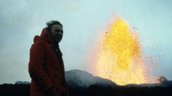 Hombre cubierto con chaqueta roja al lado de una fuente de lava