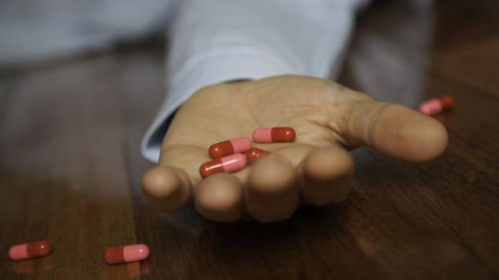 Homem segura comprimidos