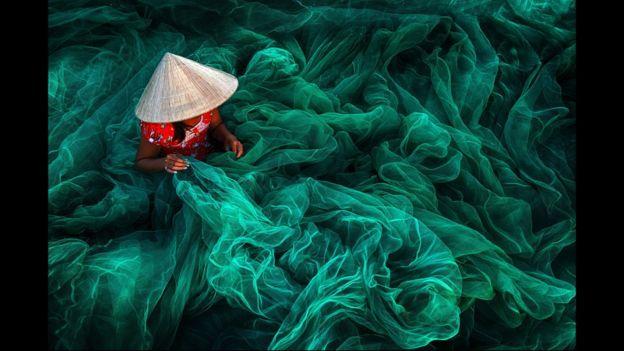Mujer tejiendo redes de pescar