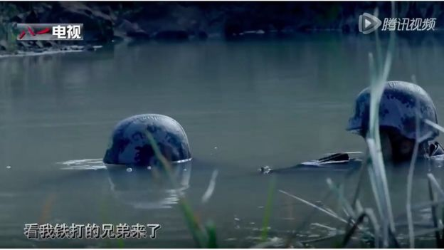 The helmets of two soldiers, poking out of a swamp
