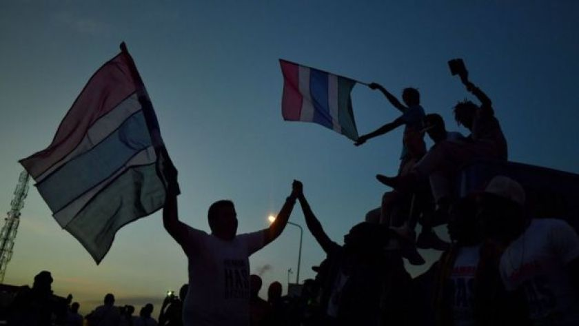 People celebrate in the streets with Gambian flags as they hear of the imminent departure of former Gambian leader Yahya Jammeh in Banjul on January 21, 2017