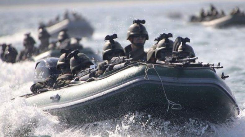 Un bote inflable lleno de soldados y otros detrás