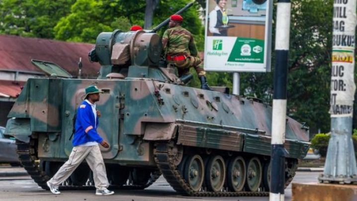 A man walks past an armoured personnel carrier in Harare on November 15, 2017