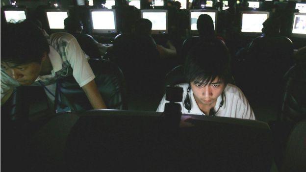 Jovem asiático em frente a computadores