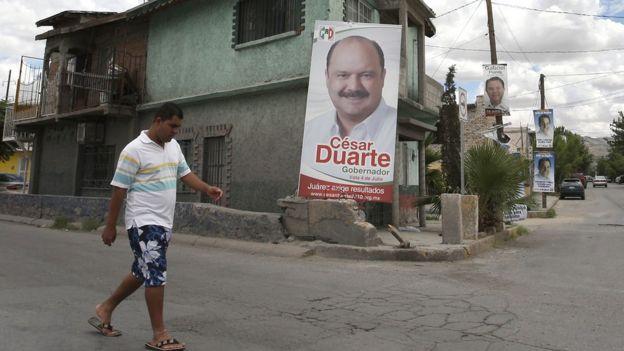Un hombre pasa por el frente de un cartel de campaña de César Duarte.