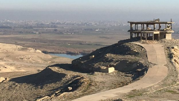 A ruined building, right, stands stop a small rise - overlooking the city of Mosul in the distance