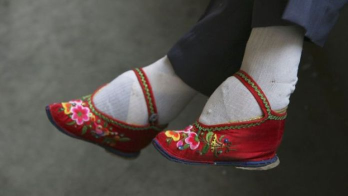 A member of the Bound Feet Women Dancing Team, wearing her 'Three Cuns Golden Lotus' shoes, prepares for dancing practice at Liuyi Village on April 2, 2007 in Tonghai County of Yunnan Province, China.