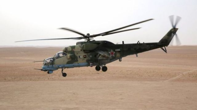 A Russian Mil Mi-24 'Hind' attack helicopter flying in the eastern Syrian region of Deir Ezzor. The landscape is an open desert.