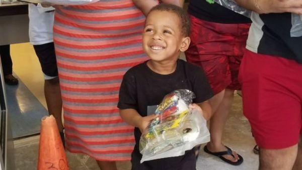 Un niño sonríe al recibir su combo en una escuela pública de Overtown.