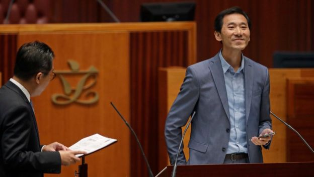 Newly elected pro-democracy lawmaker Edward Yiu Chung-yim smiles as he takes oath in the new legislature Council in Hong Kong, Wednesday, Oct. 12, 2016