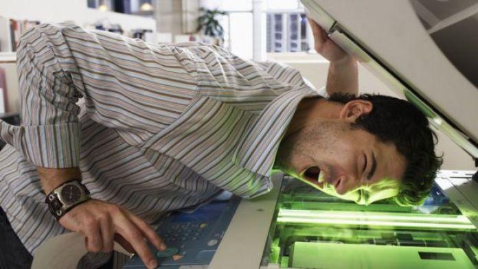 Hombre haciendo copias de su cara en una fotocopiadora