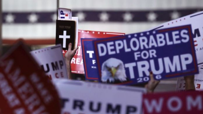 Supporters hold signs and a copy of the Bible during a rally for Republican presidential candidate Donald Trump, Monday, Nov. 7, 2016, in Manchester, N.H.